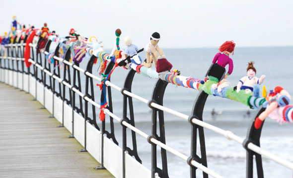 A scarf featuring woollen athletes on Saltburn pier railings